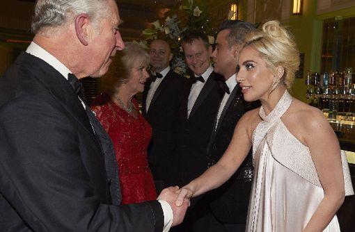 Lady Gaga und Robbie Williams schütteln königliche Hände