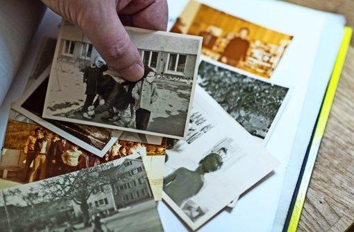 Detlev Zander betrachtet Fotos aus der zeit in einem Kinderheim der Brüdergemeinde  Korntal Foto: dpa