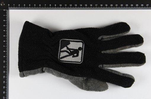 """Unbekannter überfällt Tankstelle in Böblingen. Die Polizei stellt im Zuge der Fahndung ein Paar Handschuhe sicher. Für die Kriminalpolizei ist es nun wichtig, zu erfahren, ob der Räuber die Handschuhe während seiner Flucht wegwarf oder ob sie von einem gänzlich Unbeteiligten verloren wurden. Die Handschuhe mit dem Label """"By Hornbach"""" sind aus Fließstoff. Die Handinnenseite samt Daumenpartie ist grau, der Handrücken schwarz. Auf dem Handrücken befindet sich zudem ein Symbol, das einen Bauarbeiter darstellt. Foto: Polizeidirektion Böblingen"""