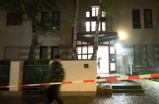 Ein Polizist steht am Dienstag in Berlin im Ortsteil Gatow vor einem Mehrfamilienhaus, in dem vier Leichen gefunden wurden. Foto: dapd