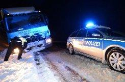Ein Polizeifahrzeug steht am Mittwoch auf der B31 im Höllental bei Hinterzarten (Baden-Württemberg) neben einem Lkw, der im Graben steckt. Starker Schneefall hat im Schwarzwald für ein Verkehrschaos gesorgt. Foto: dpa