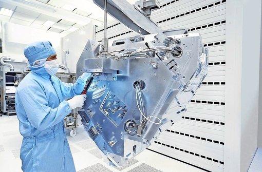 Zeiss employees in Oberkochen working on production machine. Photo: Zeiss