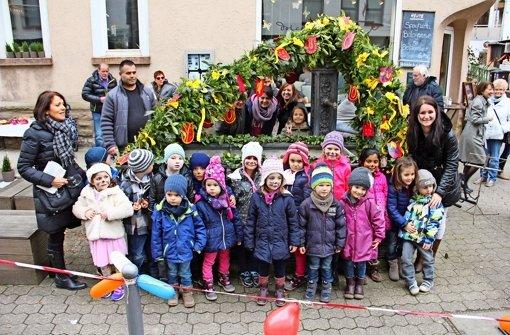 Kinder tanzen und singen vor dem Osterbrunnen