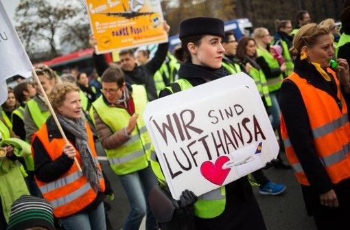 """Eine Lufthansa-Mitarbeiterin hält im November 2015 in Frankfurt am Main  bei einer Kundgebung vor Konzernzentrale der Fluggesellschaft ein Plakat mit der Aufschrift """"Wir sind Lufthansa"""". Foto: dpa"""