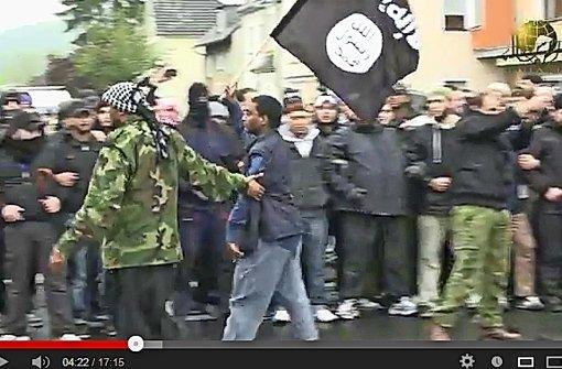 """Ein Internetvideo zeigt die Islamisten Denis Cuspert (links) und Munir Ibrahim kurz vor den Ausschreitungen in Bonn 2012. Der Pforzheimer trägt eine Fahne, die ein Jahr später zum Symbol der Terrororganisation """"Islamischer Staat"""" wurde. Foto: Youtube"""