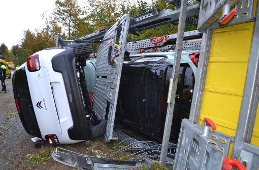 Autotransporter kippt um - Kleinwagen blockieren Straße