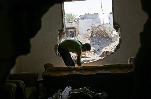 Israel und militante Palästinenser beschießen sich weiter: Dieser Palästinenser schaut in seinem zerstörten Haus im Westen von Gaza-Stadt nach Überbleibseln des Angriffs. Foto: