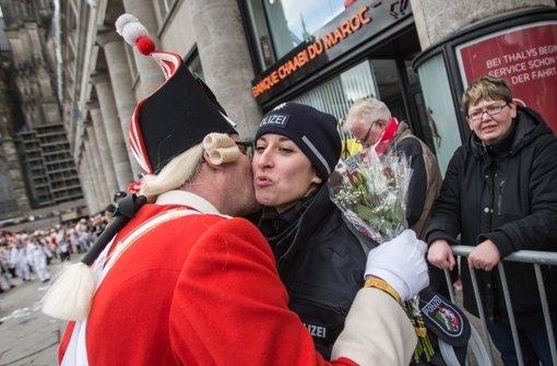 Jeck mit Kuschelbedarf: In Köln wird eine Polizistin gebusselt. Foto: dpa