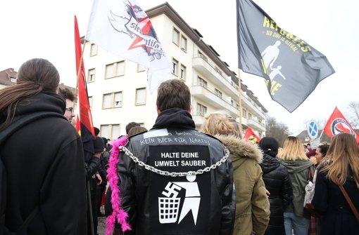 """Ein Kundgebungsteilnehmer bringt bei einer Demonstration vor einer Flüchtlingsunterkunft  seinen Protest gegen Rechtsextreme mit einem Anti-Nazi-Jackenaufdruck """"Halte Deine Umwelt sauber"""" zum Ausdruck. Foto: dpa"""