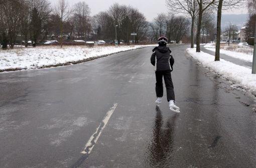 Ein Kind läuft am Sonntag in Karlsruhe auf einer komplett vereisten Straße mit Schlittschuhen.  Foto: dpa