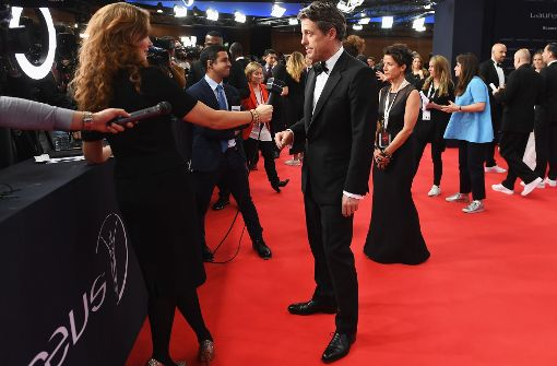 Das Schwarzbrot der Promi-Zunft: lästige Reporter-Fragen auf dem Roten Teppich beantworten. Auf dem Foto steht der Schauspieler Hugh Grant bei den Laureus World Sports Awards in Monaco Rede und Antwort. Foto: Getty Images Europe