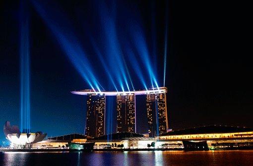 Wie auf einem anderen Planeten: Das dreitürmige Hotel Marina Bay Sands bestimmt das Bild am Hafen von Singapur, links daneben das muschelartige Kunstmuseum, davor das Kongresszentrum. Foto: SoAk/Kern