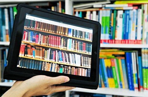 Ein Tablet-PC vor einer Regalwand. Immer mehr Bücher werden digital heruntergeladen und gelesen. Den E-Book-Boom treiben auch Autoren an, die ihre Werke selbst verlegen. Foto: dpa