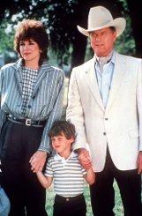 Fiesling J. R. Ewing (Larry Hagman (r) mit seiner Frau Sue Ellen (Linda Gray) und Sohn John Ross (Omri Katz) in der US-Fernsehserie Dallas. (Foto undatiert) Foto: dpa