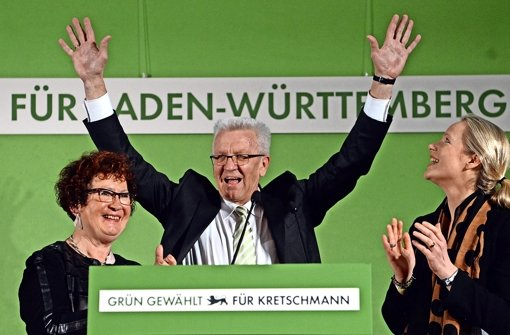 Lässt sich auf der Wahlparty der Grünen in der Stuttgarter Staatsgalerie feiern: Winfried Kretschmann – links Ehefrau Gerlinde, rechts Grünen-Landesvorsitzende Thekla Walker. Foto: dpa