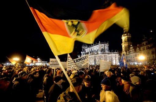 Anhänger des Pegida-Bündnisses (Patriotische Europäer gegen die Islamisierung des Abendlandes) demonstrieren in Dresden gegen die angebliche Überfremdung durch Flüchtlinge und schwenken eine Deutschlandfahne. Foto: dpa