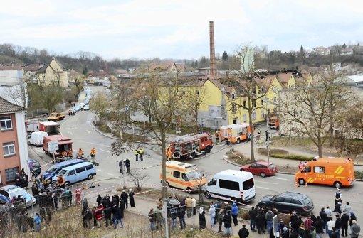 Schaulustige und Rettungskräfte bevölkern den Unglücksort in Backnang: In der alten Lederfabrik (gelbes Gebäude) starben sieben Kinder und deren Mutter. Foto: dpa