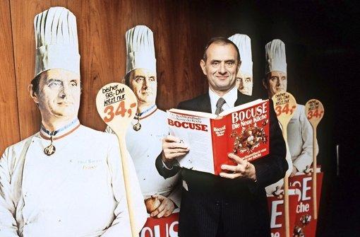"""Starkoch Bocuse in früheren Jahren mit seinem bekannten Kochbuch """"Nouvelle Cuisine"""" – auf Deutsch """"Die Neue Küche"""". Foto: dpa"""
