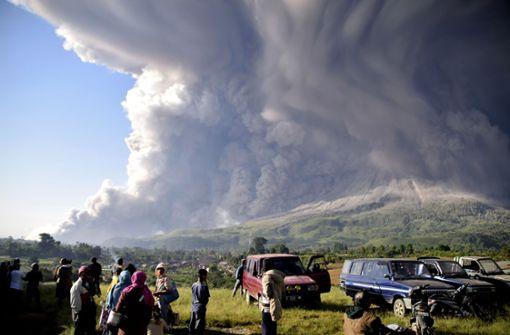 Orang-orang menyaksikan letusan gunung berapi Sinabung.  Gunung berapi setinggi 2.500 meter ini merupakan satu dari lebih dari 120 gunung berapi aktif di Indonesia.  Foto: Tidak terakreditasi / AP / dpa