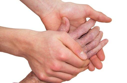 Ein Pfleger hält die Hand eines Todkranken Foto: fotolia