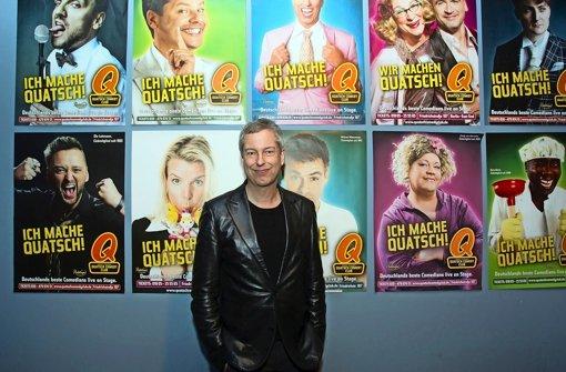 Thomas Hermanns, der  1992 den Quatsch Comedy Club in Hamburg gegründet hat, lässt sich in der Stuttgarter Spardawelt vor Plakaten seines  Erfolgsformats fotografieren Foto: Christian Hass
