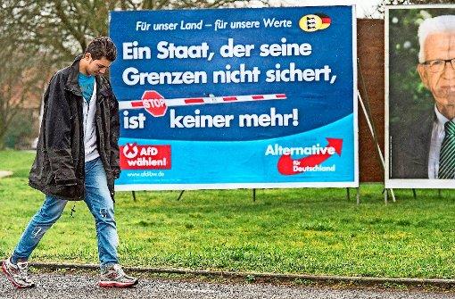 Ein syrischer Flüchtling geht an einem Wahlplakat der AfD vorbei – sie wirbt mit Kritik an der Asylpolitik für sich. Foto: dpa