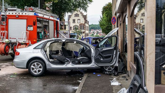 Zwei Autos rasen in Schaufenster