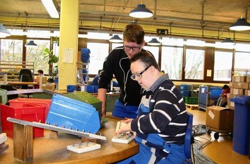 Hirschmann-Azubi Constantin Hau (hinten) hilft Thorsten Bauder in der Industriemontage der Schubert-Werkstätten in Bonlanden. Foto: Jens Noll